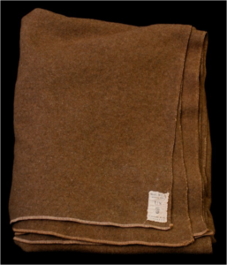 "Woolen blanket manufactured by the Mianus Manufacturing Co. of CosCob, under a contract awarded on 20 July 1917. The label has the ""flaming bomb"" logo of the U.S. Ordnance Dept. (Accession #2016.539)"